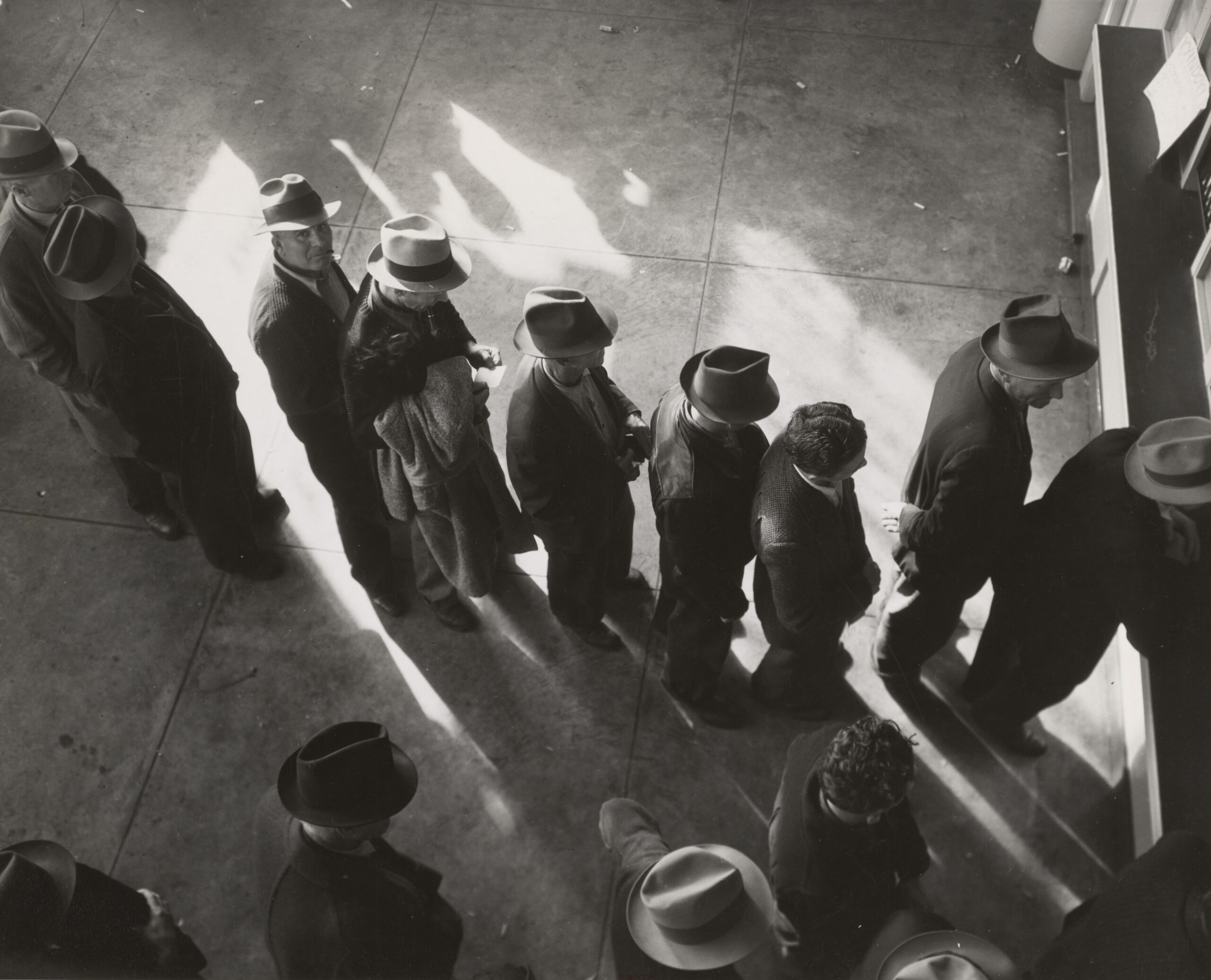 1938 - Unemployment benefits aid begins. Line of men inside a division office of the State Employment Service office at San Francisco, California, waiting to register for benefits on one of the first days the office was open. Photographer - Dorothea Lange