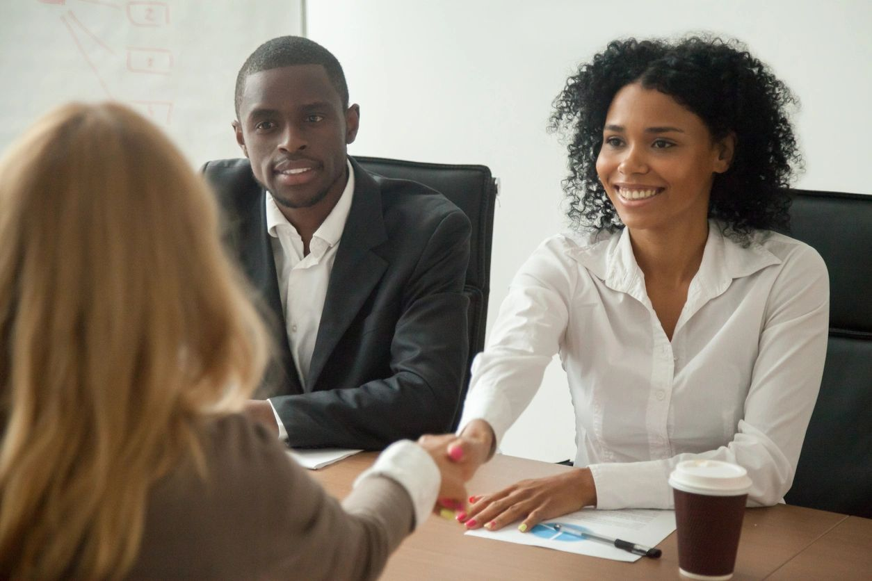 Two business women shake hands next to a business man over a conference table.