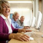Two older men and one older woman sit at computers, smiling.