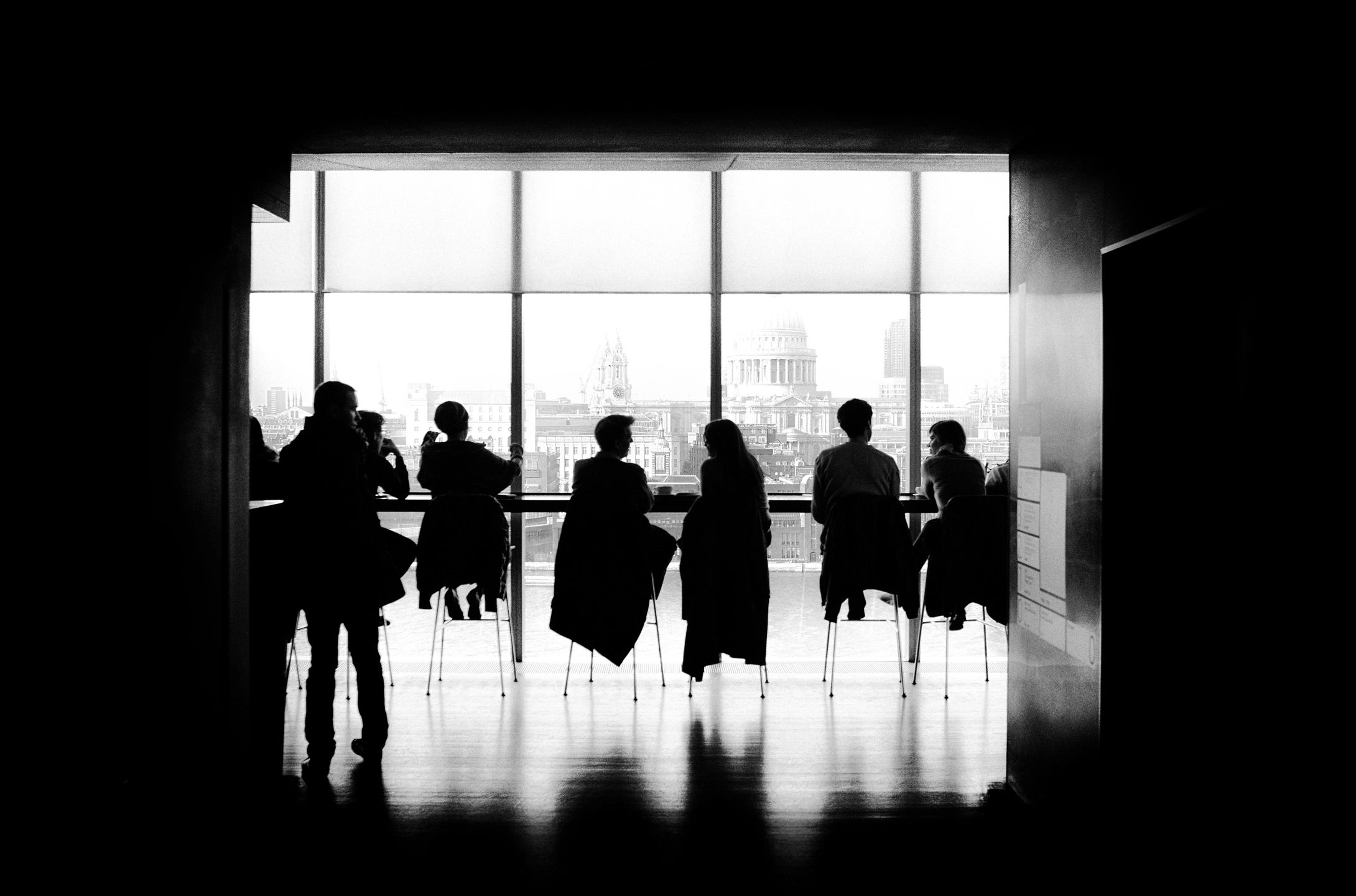 People sitting in chairs side by side in silhouette against a window.
